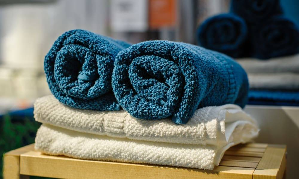 blue towels rolled up on top of folded white towels