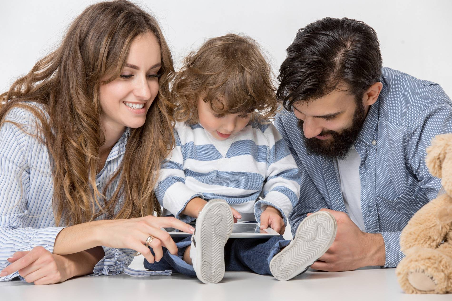 Mother, father, and child looking at an iPad