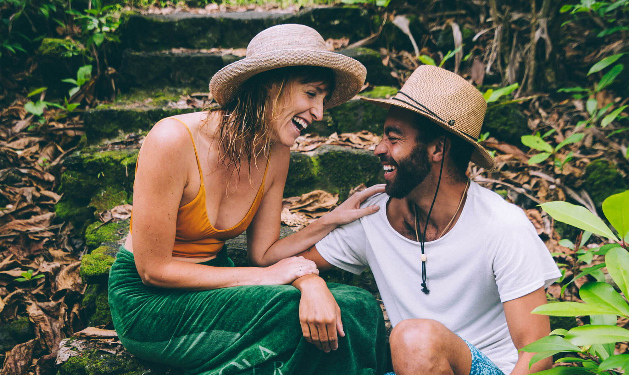 Man and woman laughing wearing sun hats
