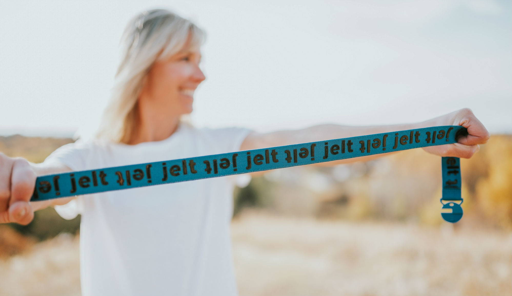 Jelt is a Certified B Corporation. Featured is a women showing the strength of the elastic belt by stretching it.