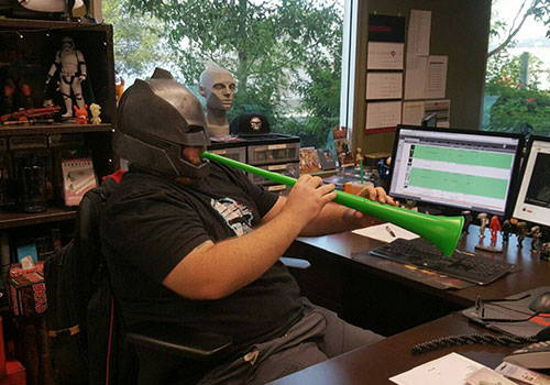 Photo of a J!NX employee playing a toy horn at his desk