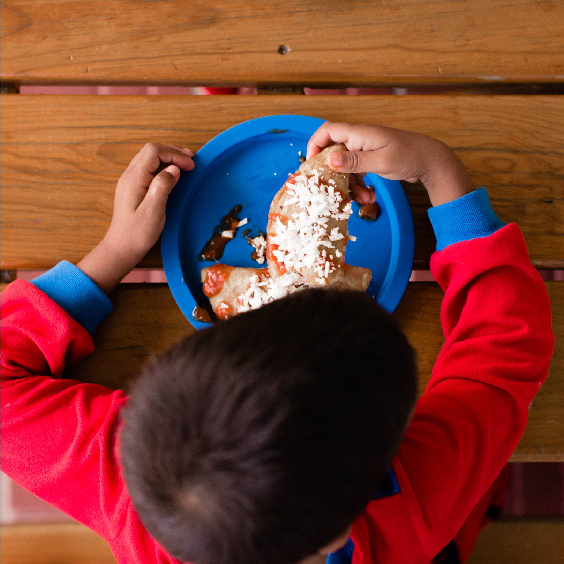 A young Honduran boy in a red shirt sits at a picnic table while eating two empanadas