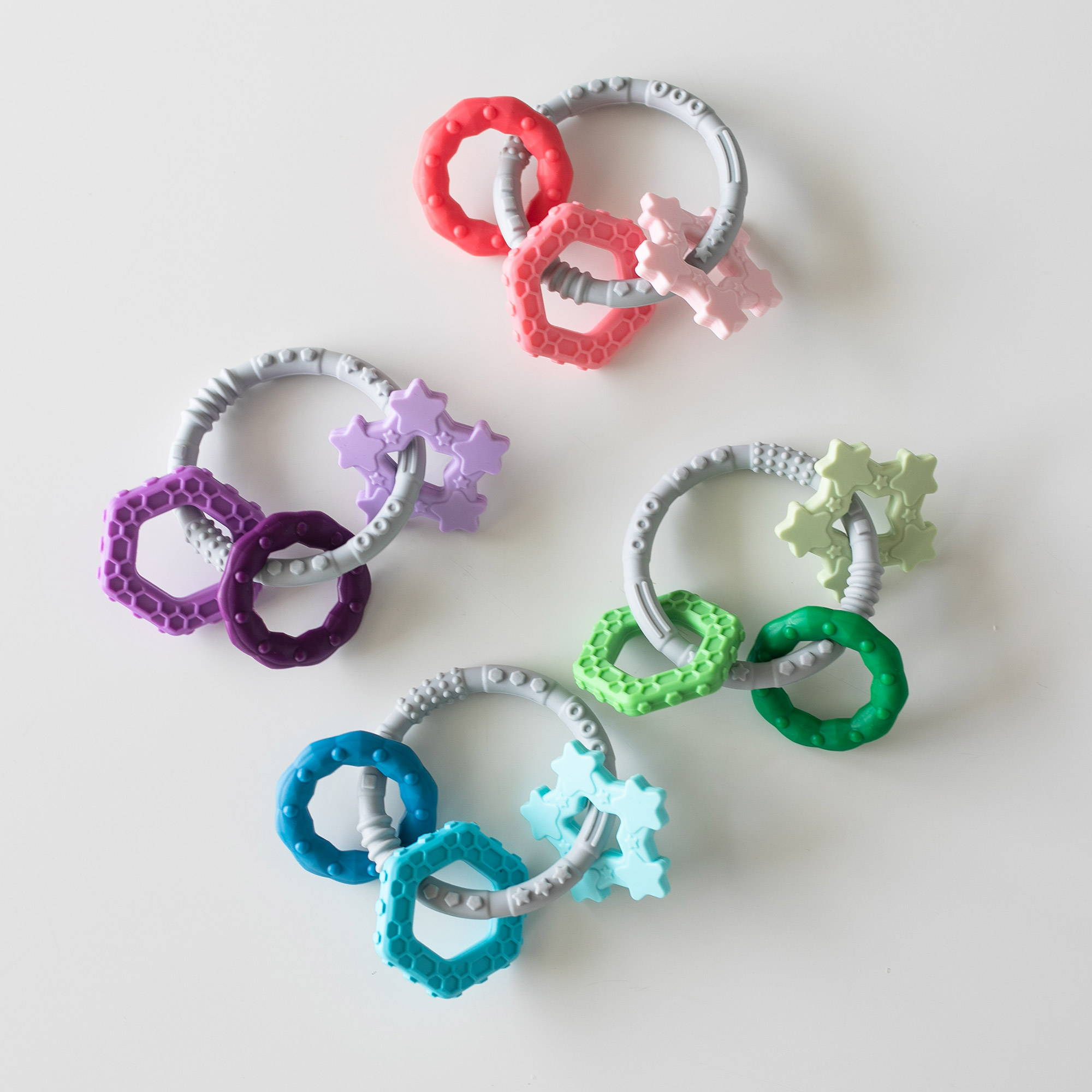 green, blue, purple, and pink shaped textured baby teethers