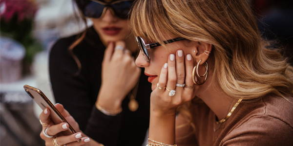 Models wearing RC fine jewelry looking at their phone