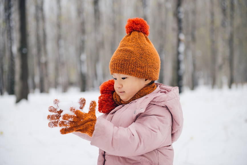 toddler with snow in hands