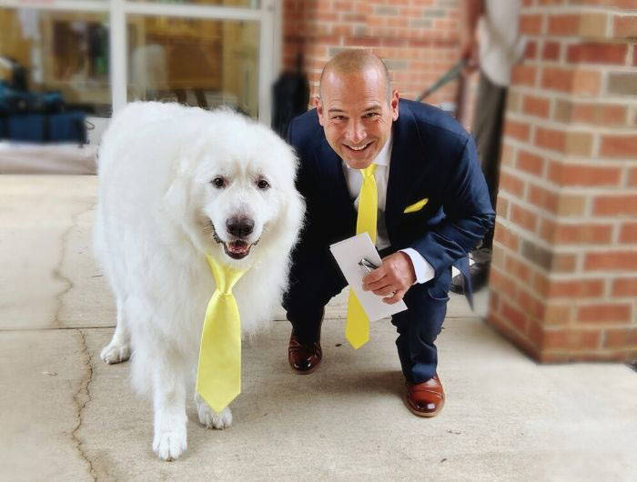 Groom wearing a matching yellow necktie with his dog