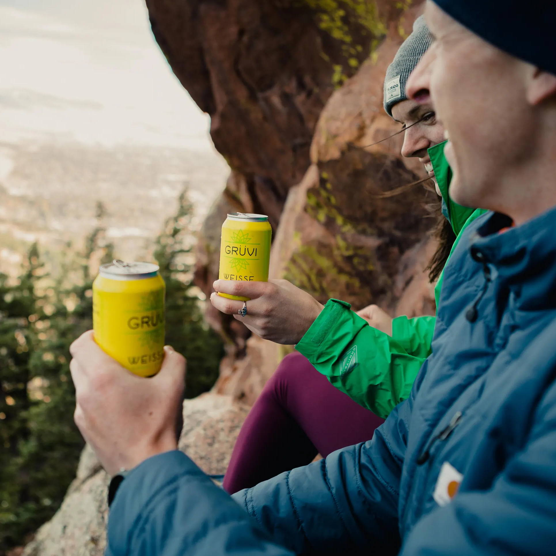 Two friends smiling as they sit on top of a mountain overlook, each holding a can of Grüvi.