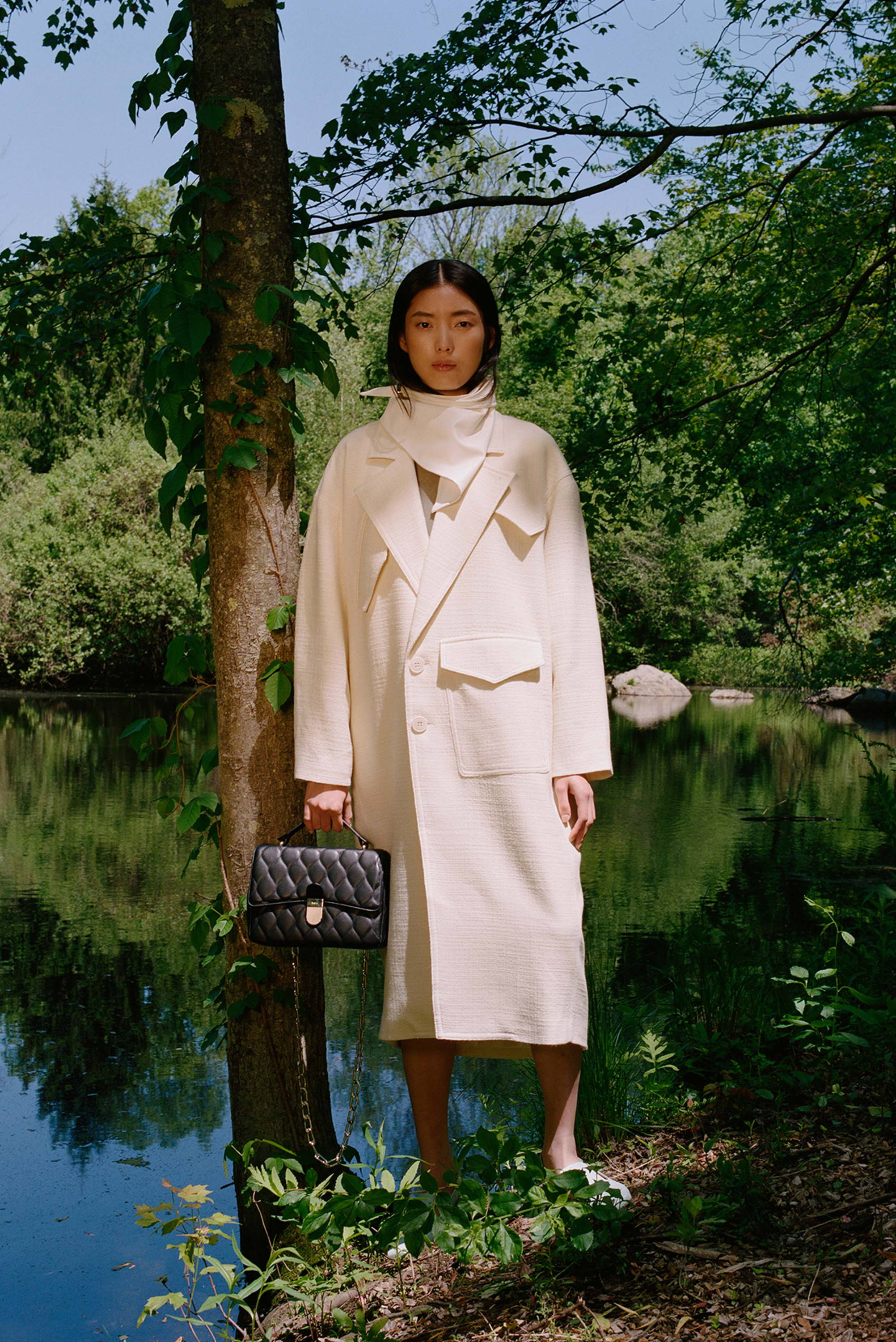 Model standing on front of pond wearing white coat and white leather bandana. She is holding a black quilted bag.