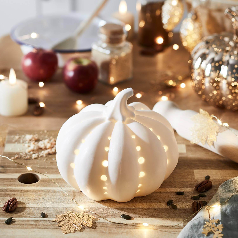 Illuminated ceramic pumpkin on autumnal table