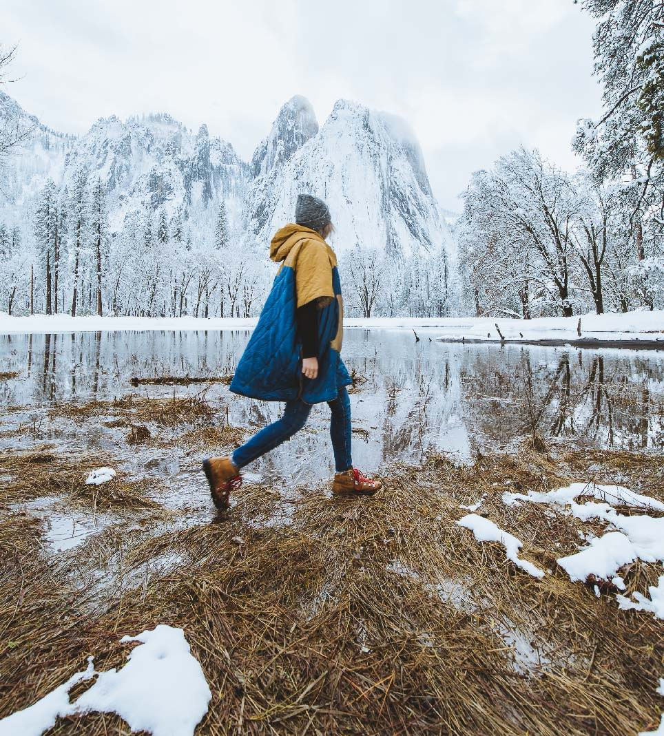 girl walking in original puffy poncho by iconic Yosemite snow covered mountains