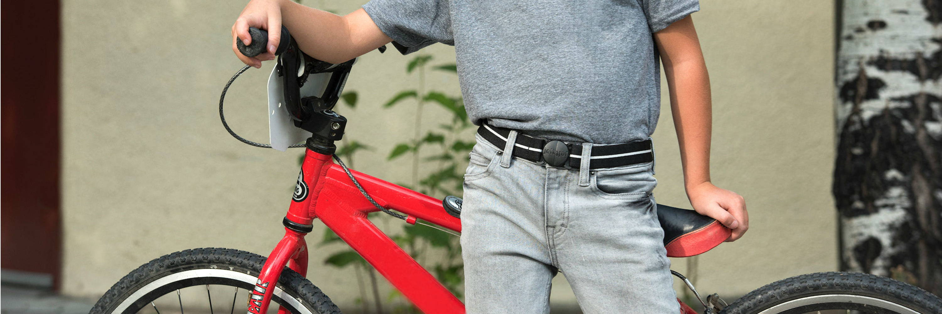 Jelt Junior belt collection sized for kids ages 5 and up. Photo of boy and his bike wearing Jelt Junior in Back in Black Stripe belt.