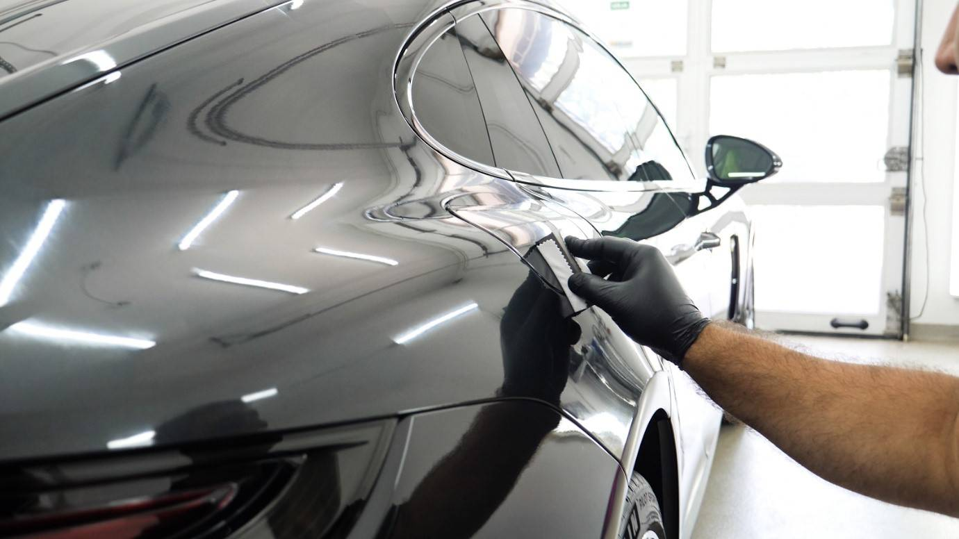 A man applying auto ceramic coating to a car in a garage