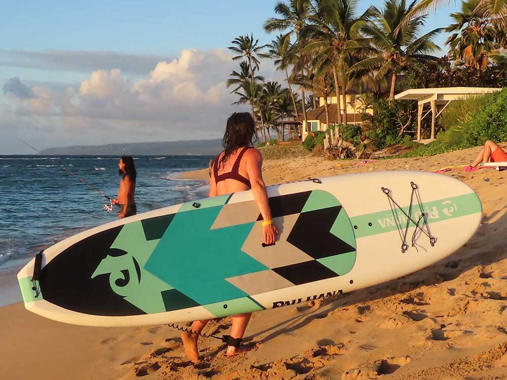 Carrying the Big EZ Hawaiian stand up paddle board down a beach