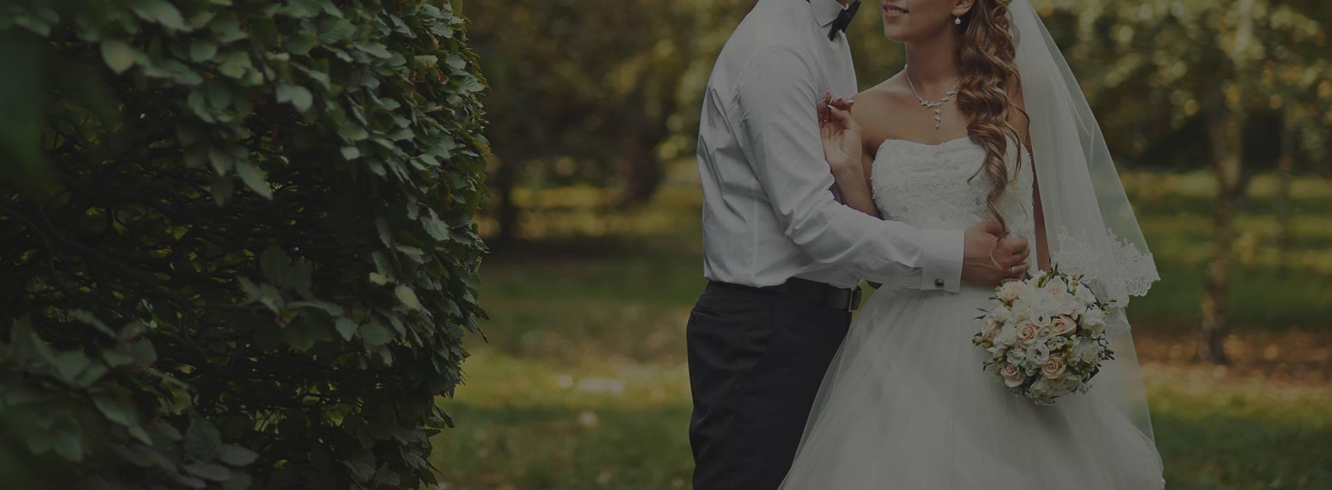 Wedding Groom and Bride embracing near greenery