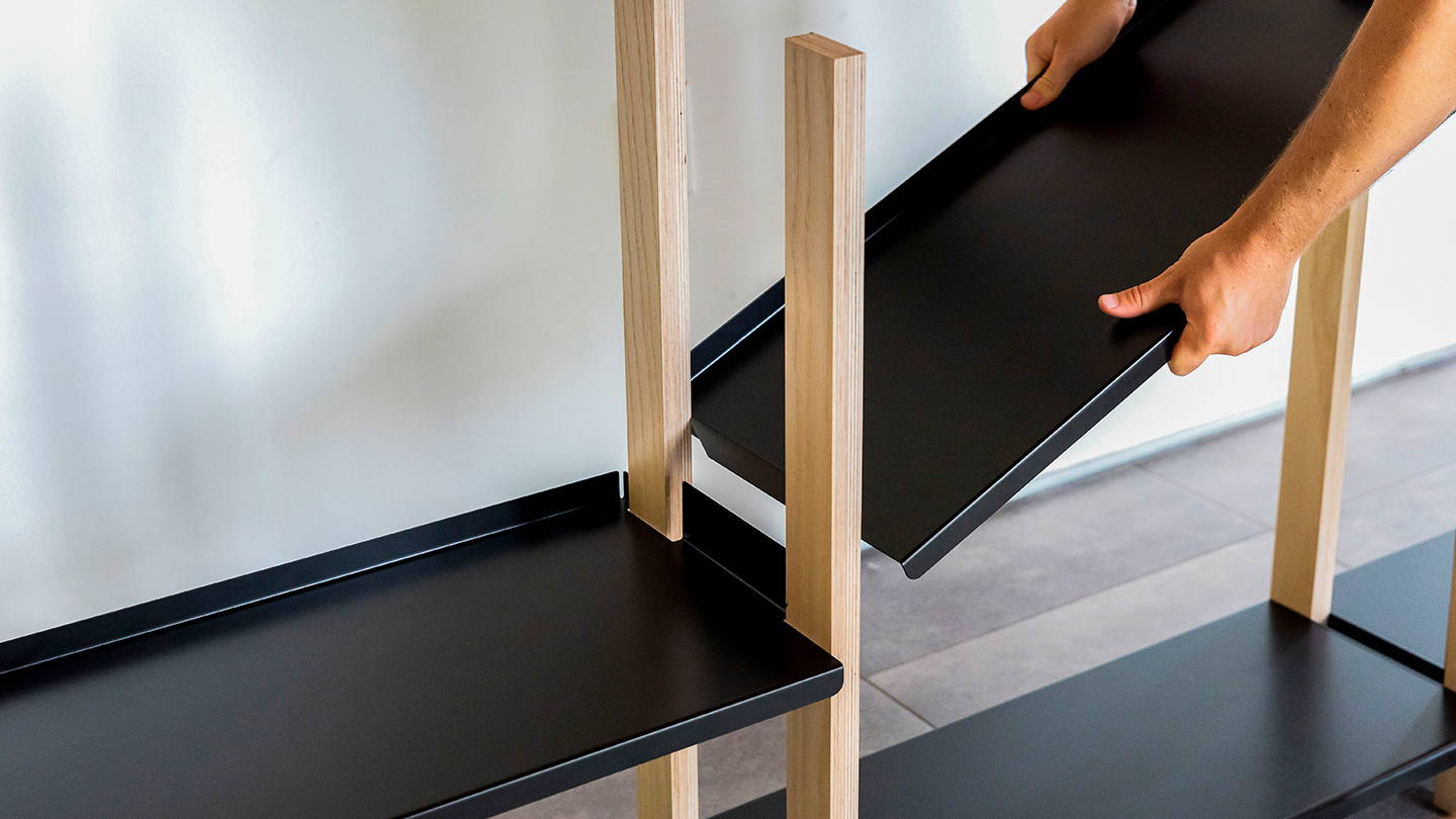 A black shelf being assembled onto The Shelving System