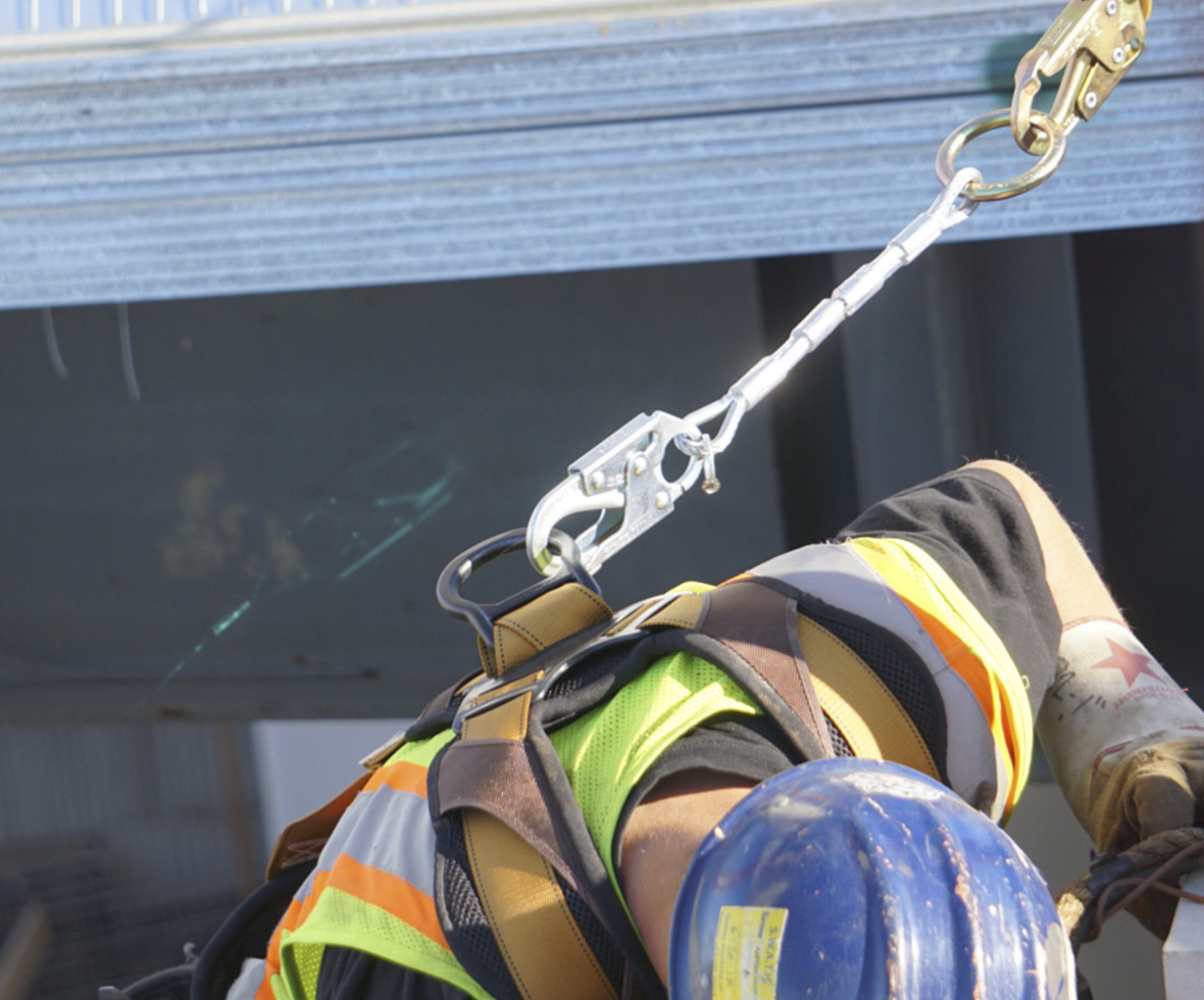 Ironworker bending down that has a cable D-ring extender and a leading edge lanyard attached to his harness