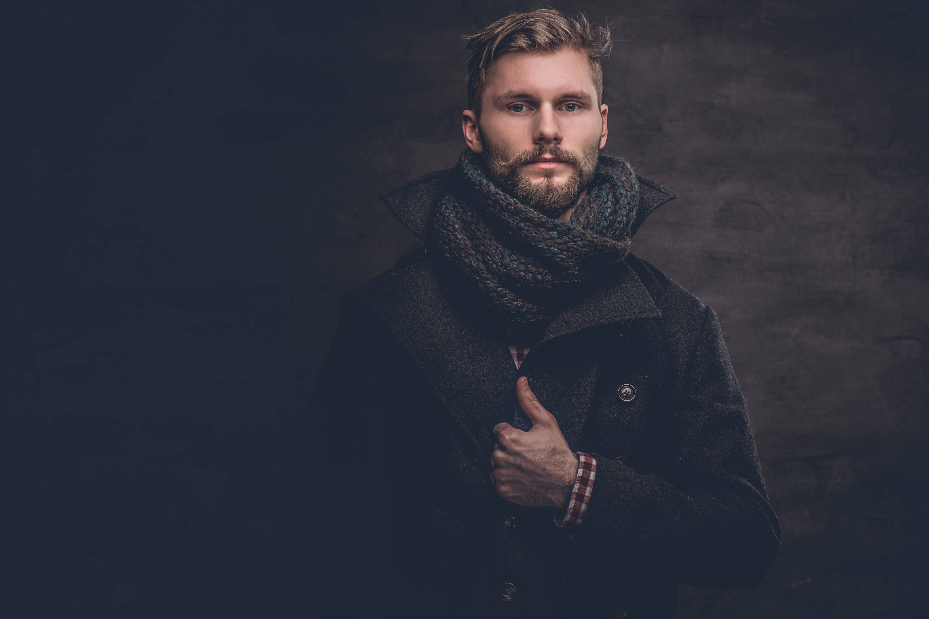 Well dressed young man layers boiled wool coat with chunky scarf for a hip, homespun style