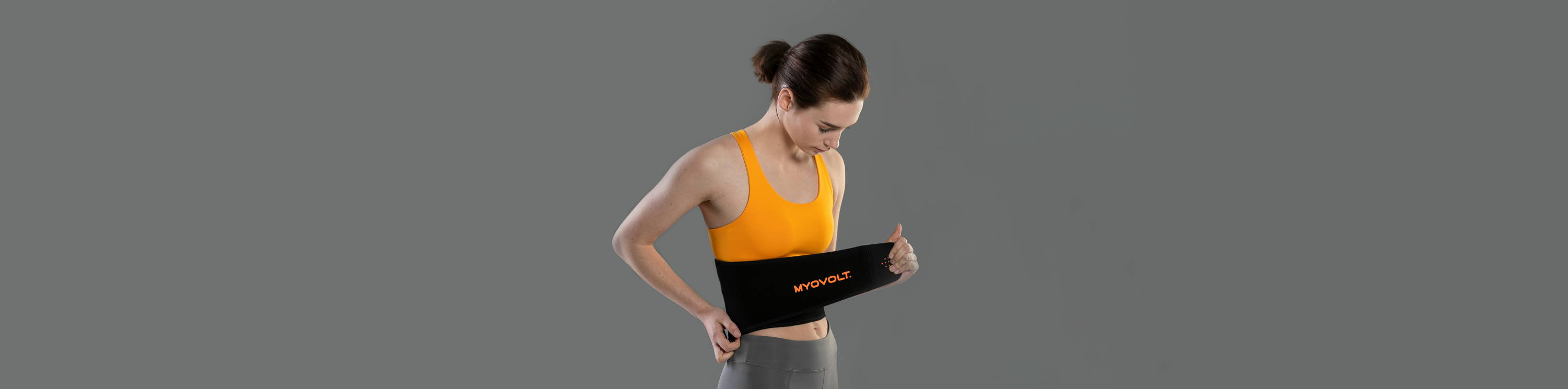 Woman looking down at waist as she straps on Myovolt Back