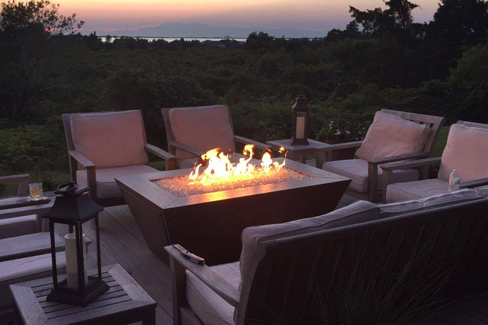 A Copper Creek fire pit illuminates this upper deck patio view of the forest beyond.