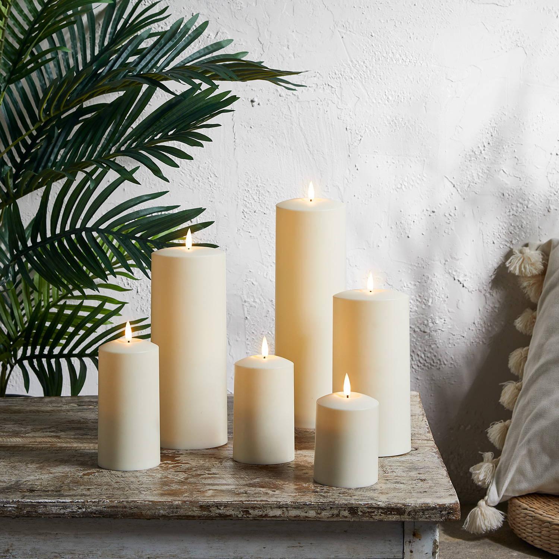 Lot de 6 bougies d'extérieur TruGlow posées sur table en bois.