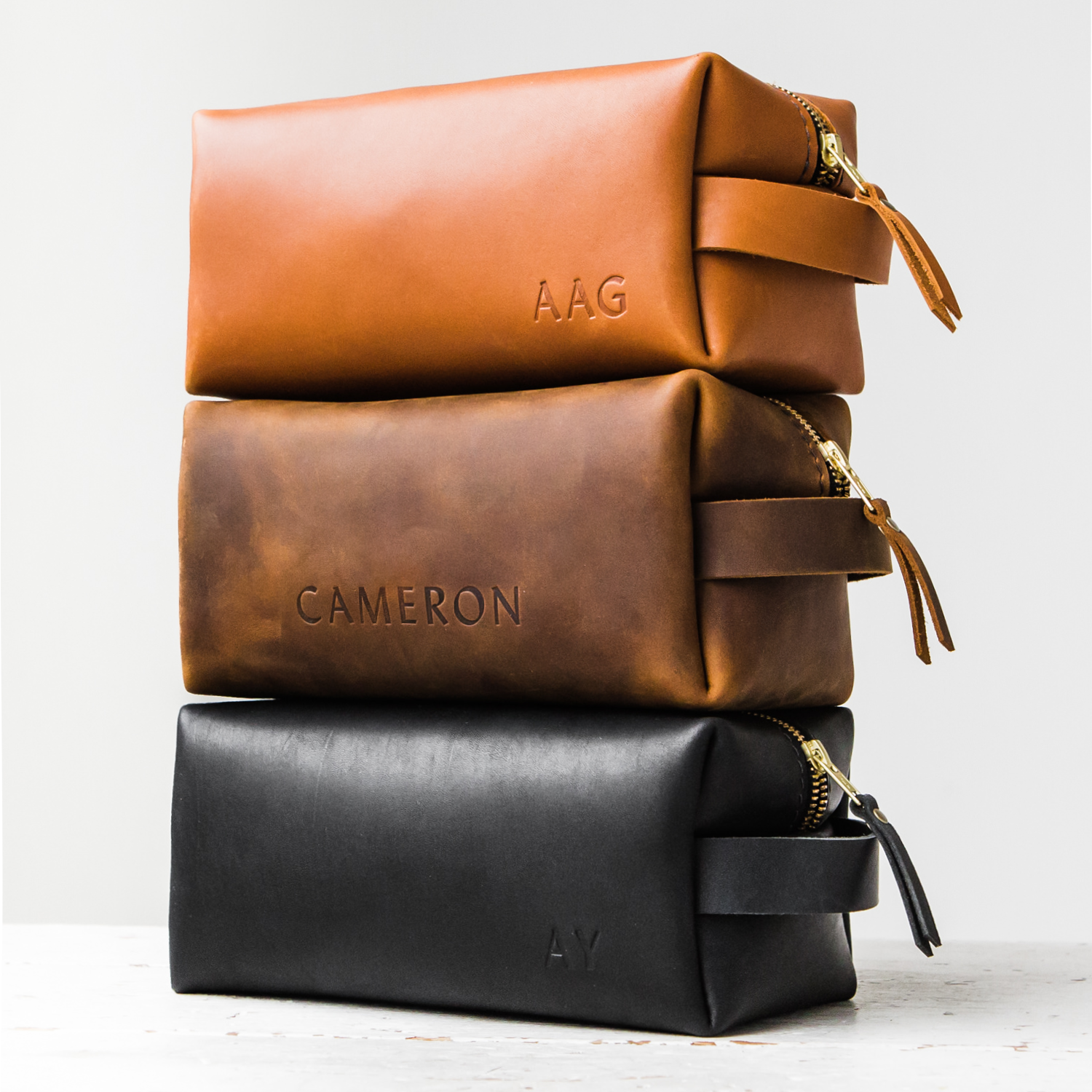 a stack of three different colors of handmade leather dopp kits made by portland leather goods