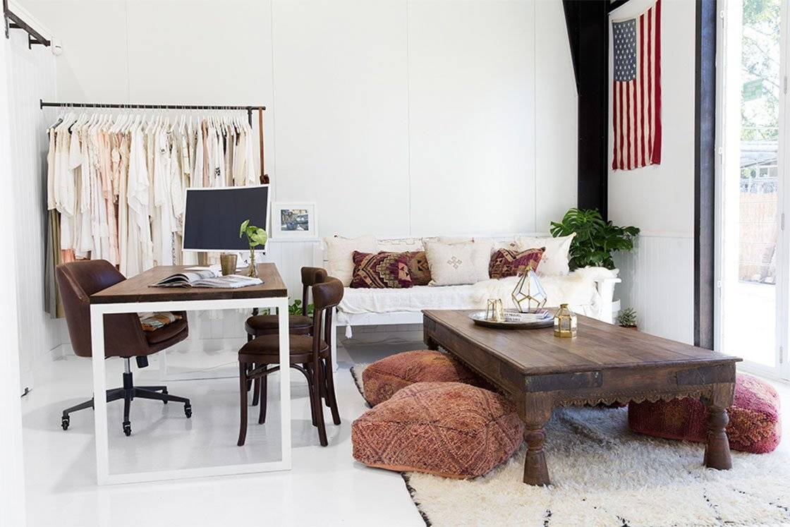 A light white office space featuring a desk with computer, coffee table with floor pillows, a white couch and a rack of clothes.