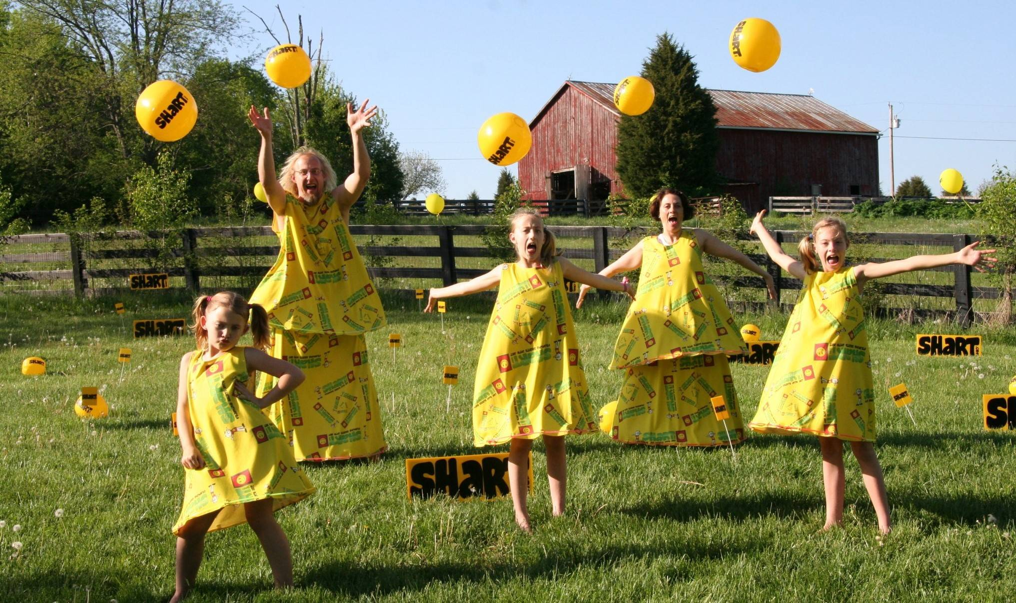 The Shart Family in large yellow dresses jumping up  and celebrating the grand opening of Shart.com