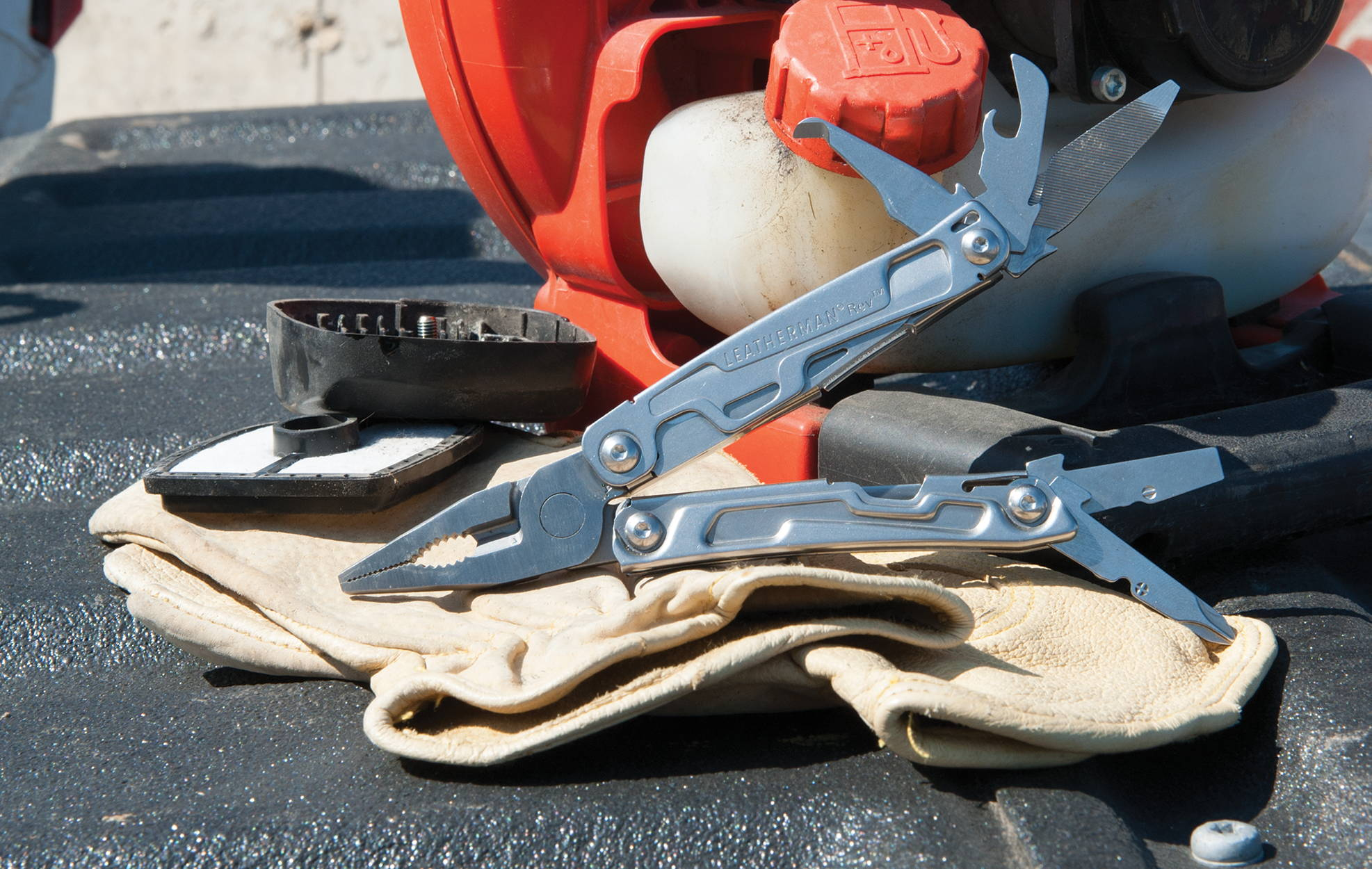 Multi-purpose tool on top of work gloves in truck bed