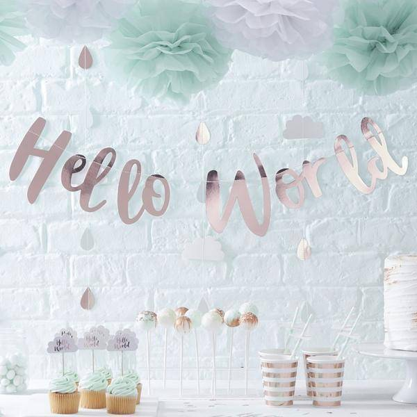 A baby shower decorated with Hello World party supplies, showing a table with the Hello World rose gold cups, the Hello World banner and baby shower pom poms, plus cupcakes and other party supplies.