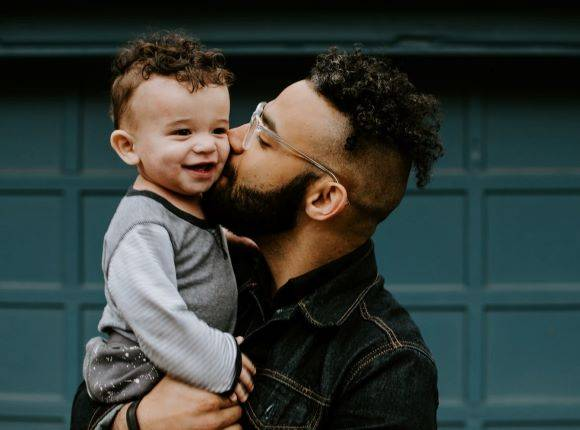 Man Carry Baby Boy And Kissing Him On The Cheek