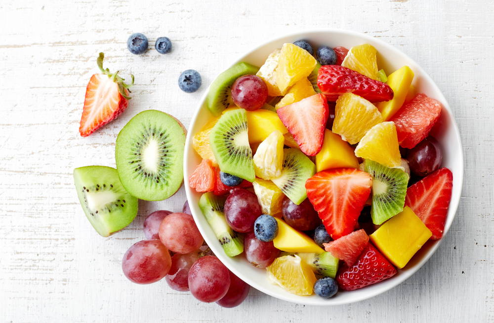 Bowl of healthy fresh fruit salad on wooden background. Top view.|siggn you have a enzyme deficiency