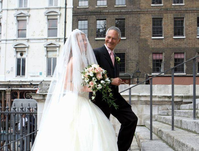 Father of bride walking up step with daughter