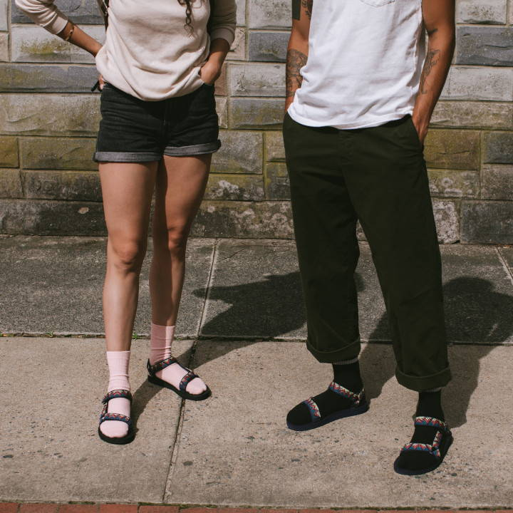 man and woman wearing Teva sandals and socks