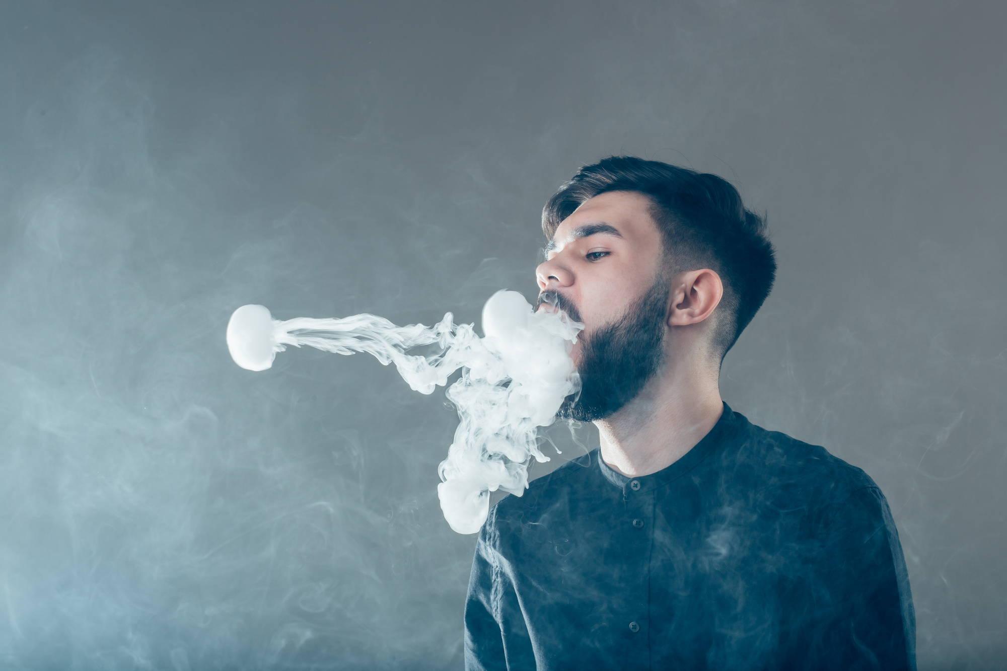 Man blowing beautiful smoke rings