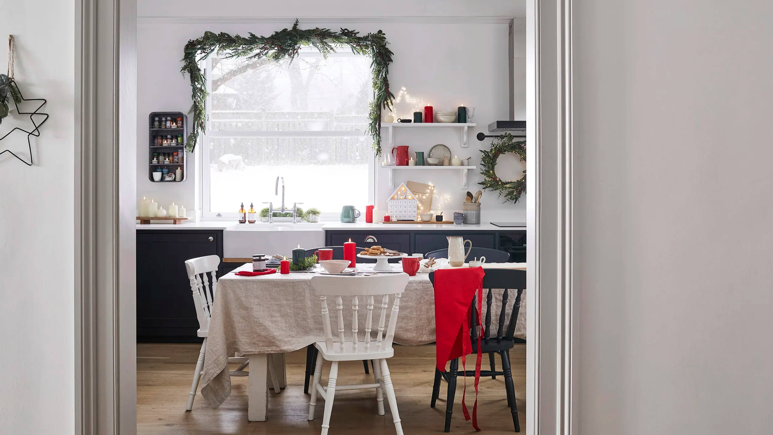 Christmas kitchen setting with Osby stars illuminated on shelves with light up house advent calendar and TruGlow candles distributed in between