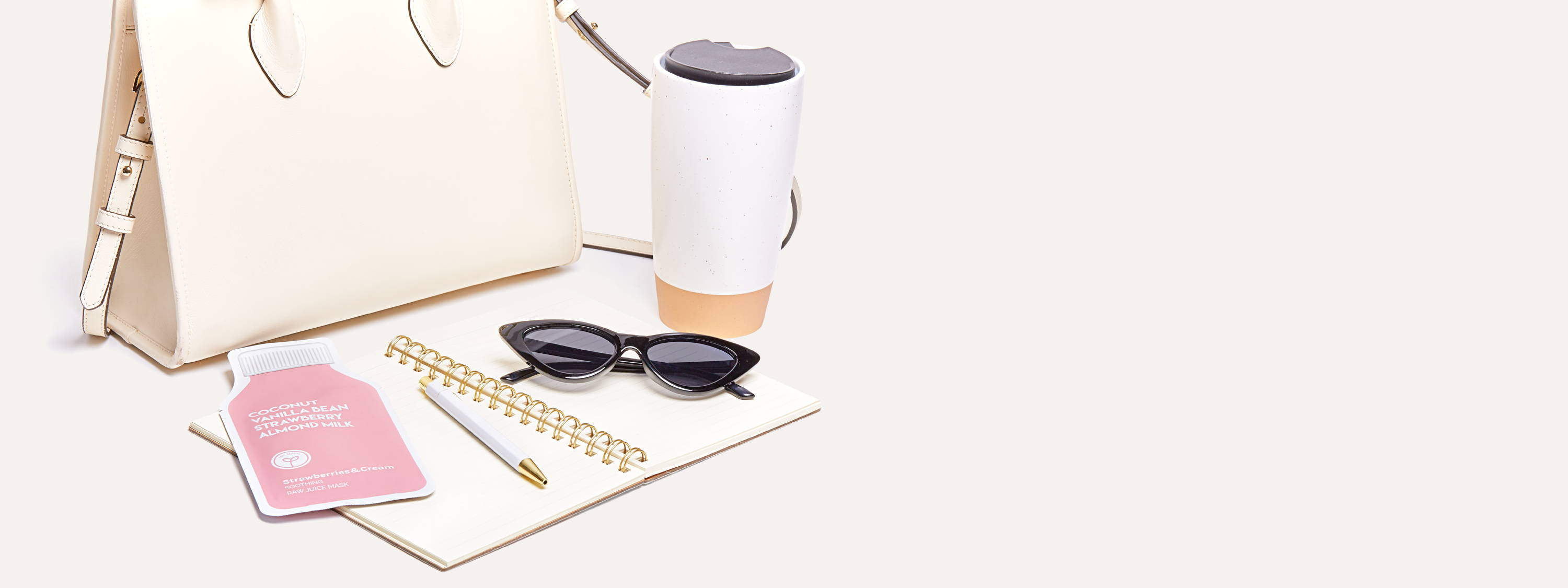 """Cream colored purse,  opened spiral notebook, gold and white pen, black sunglasses, a reusable togo coffee cup, and light pink skincare sheet mask pouch, juice bottle shape with text Coconut, Vanilla Bean, Strawberry, Almond Milk, company logo graphic of sprout inside a white circle, and text """"Strawberries & Cream"""" on a white background."""