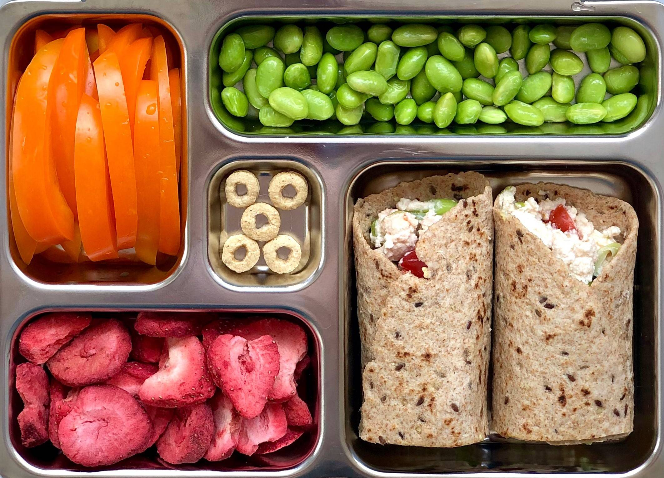 Kids lunch box filled with stuffed tuna wrap, shelled edamame, orange bell pepper sticks, freeze-dried strawberries, whole grain O's.