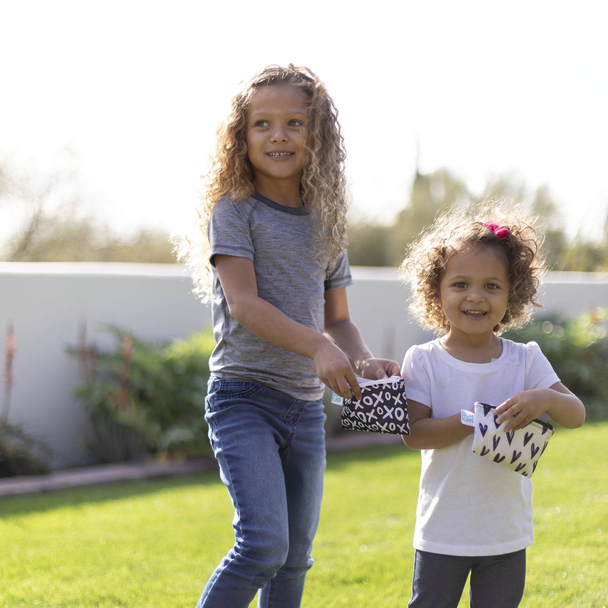 two young girls playign outside while eating snacks out of their bumkins small snack bags