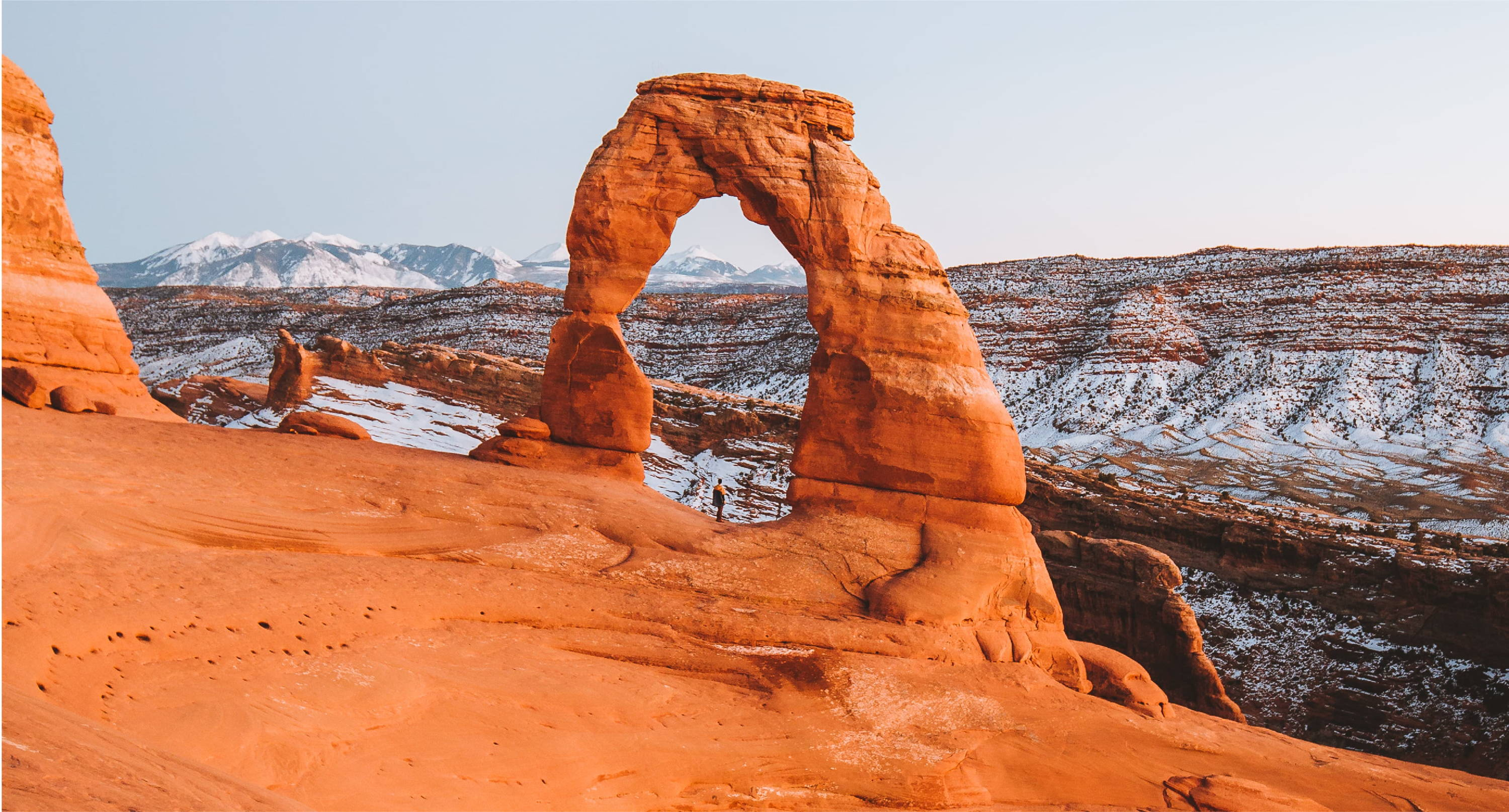 person standing underneath delicate arch