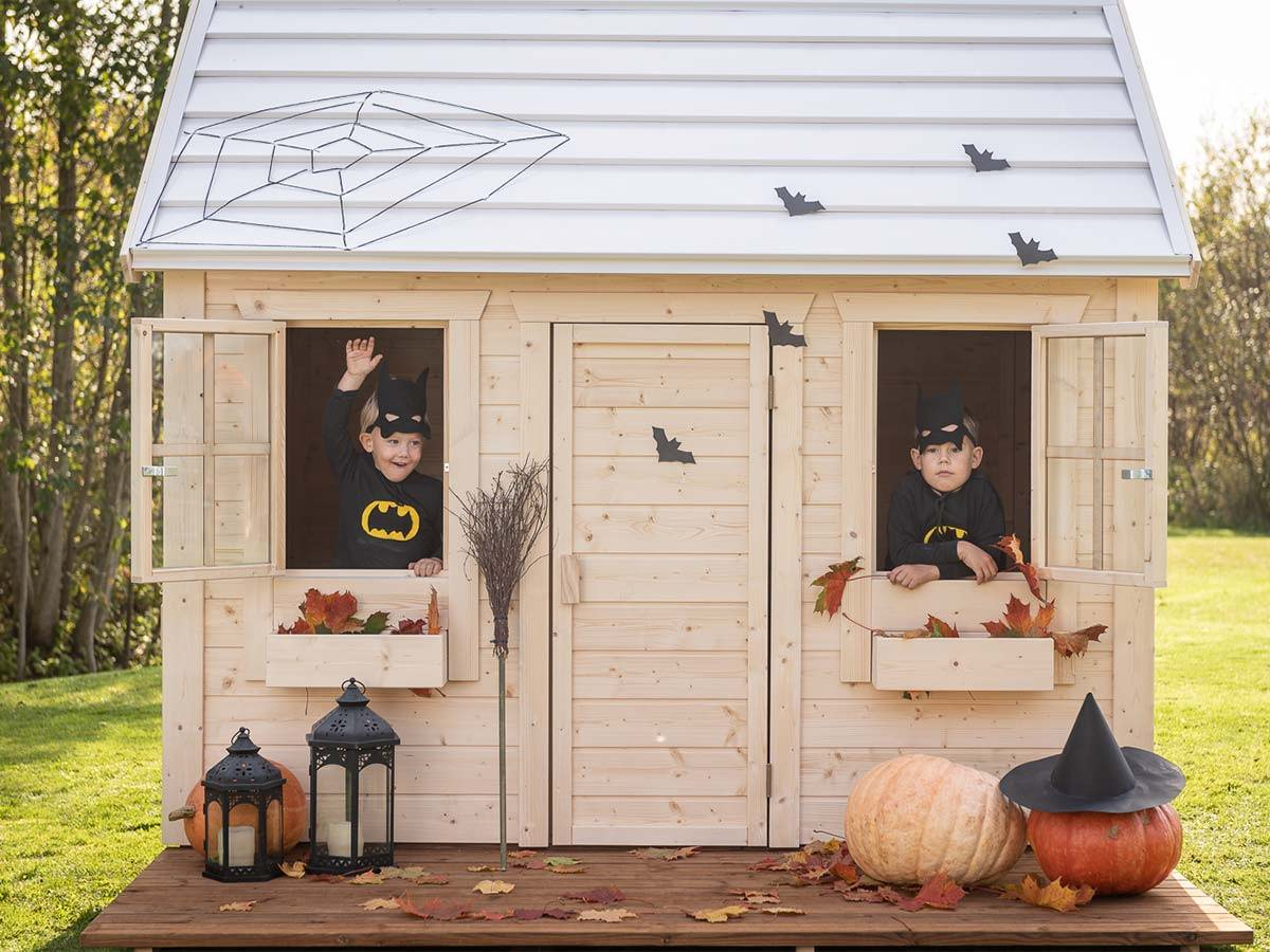 Wooden Playhouse with Halloween decoration with two boys at the windows and two lanterns and a big pumpkin in front by WholeWoodPlayhouses