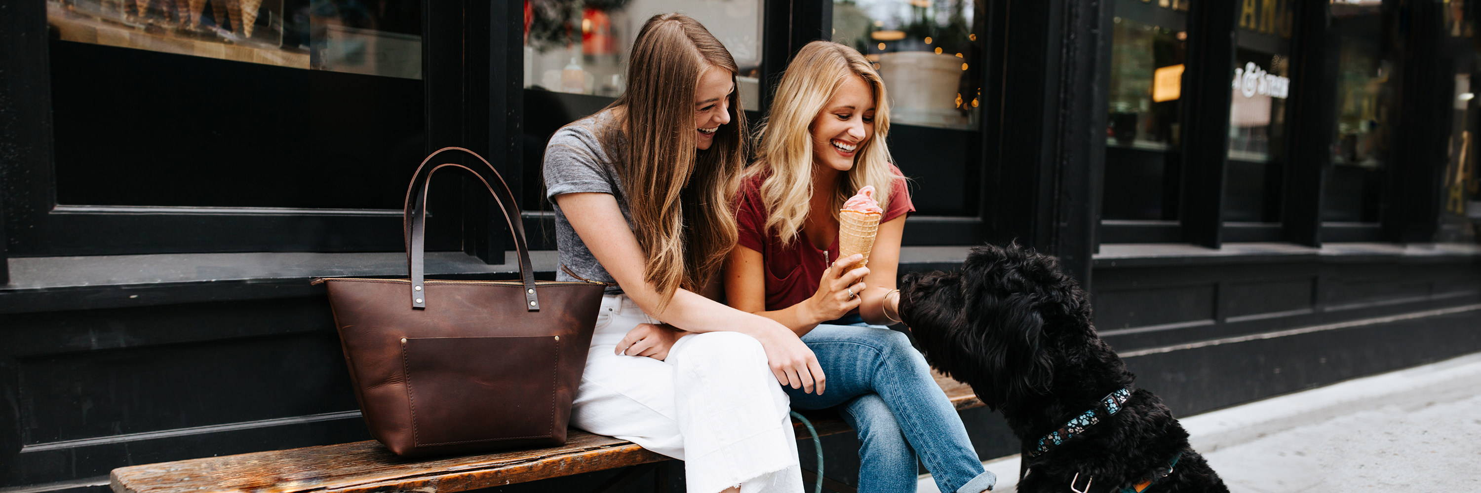 two smiling women eating ice cream cones and playing with a dog next to a handmade grizzly leather zipper tote bag by portland leather goods