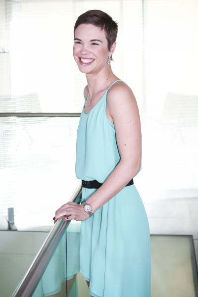 Rachel Polla standing in blue dress smiling, arms on hand rail, short brown hair