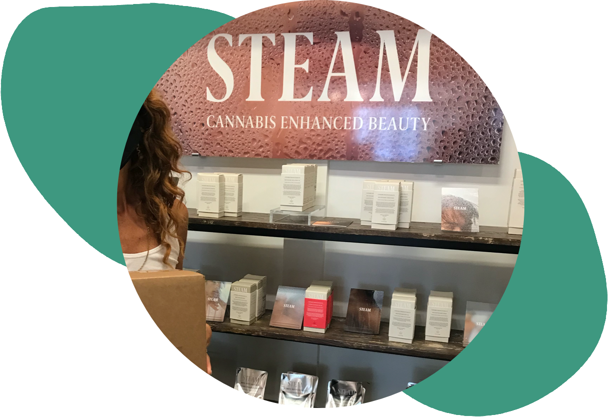 steam products displayed in their packaging on wood shelves in a circular image over abstract green shapes
