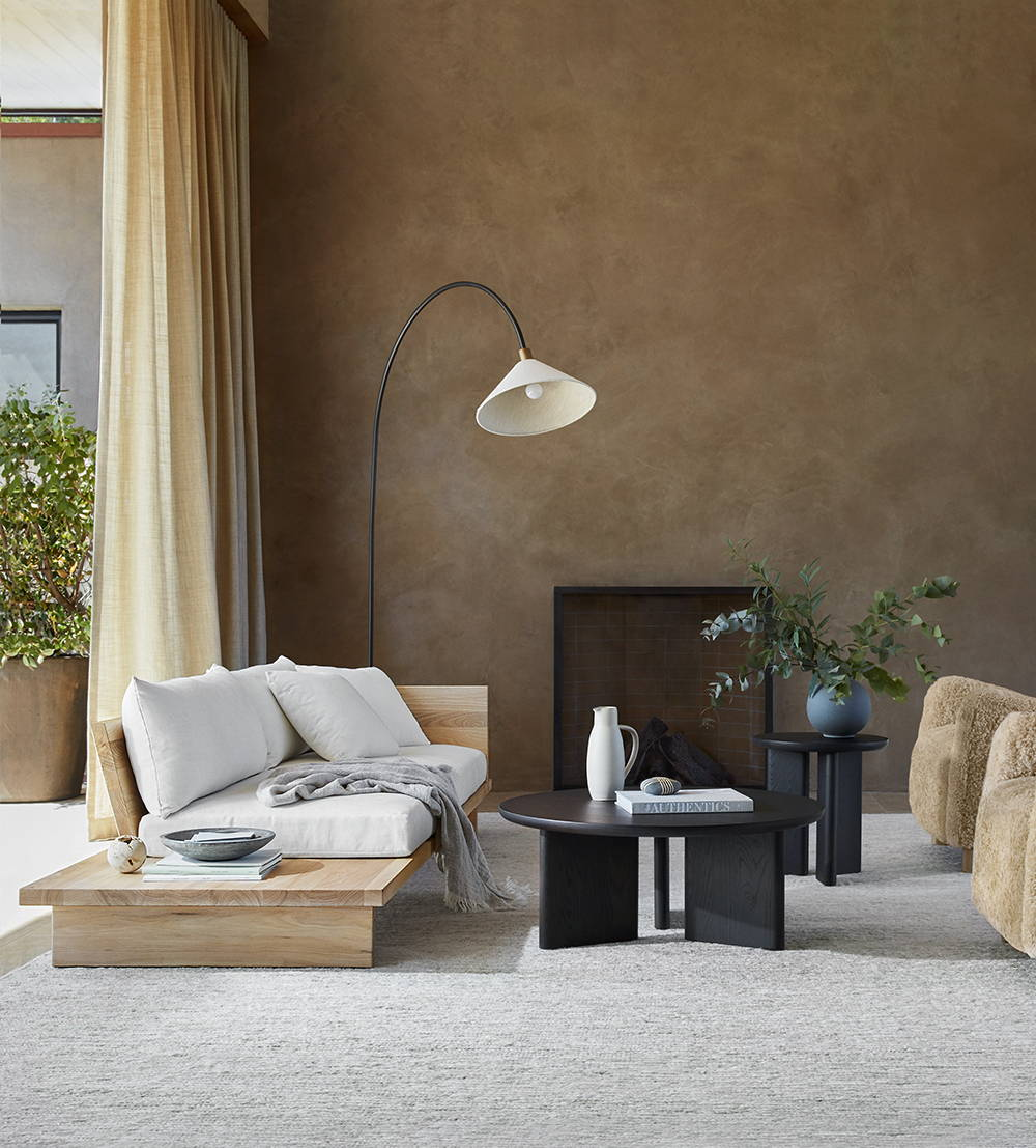 A living room furnished with a Muir sofa in Alabaster performance chenille and natural ash finish, a large and medium Morro table in Charcoal, and a Perry chair in Sandstone shearling.