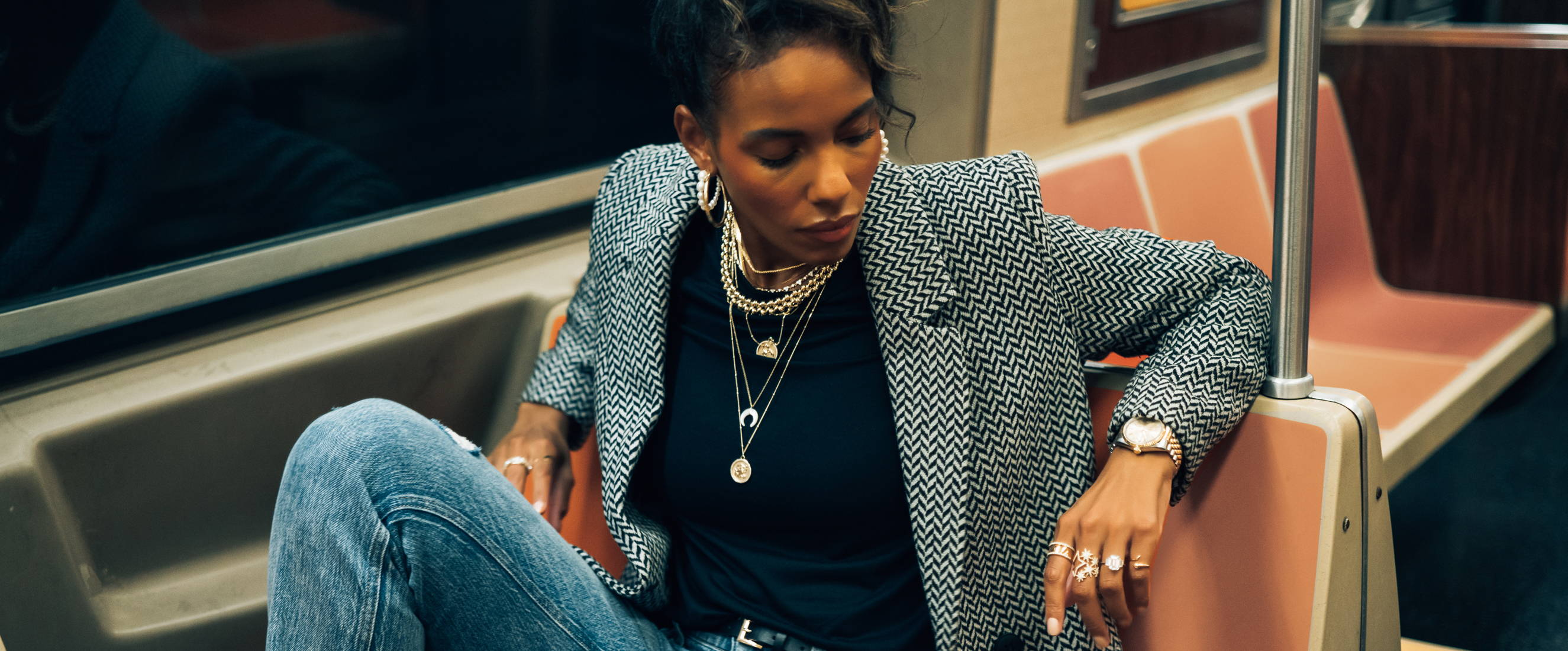 Model wearing Ring Concierge jewelry on a NYC subway