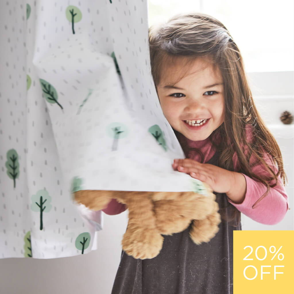 young girl holding woodland print blackout curtains