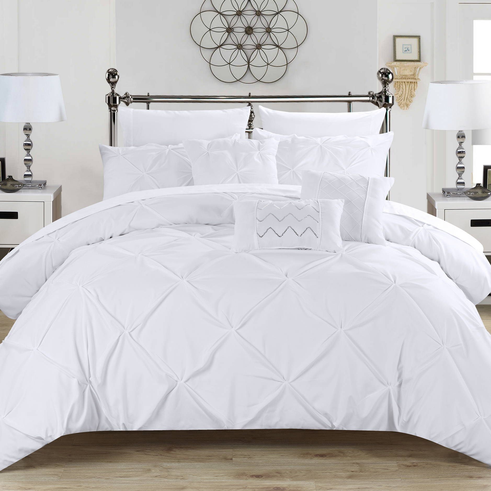 A bed with the white Chic Home Hannah pinch pleat comforter set and decorative pillows