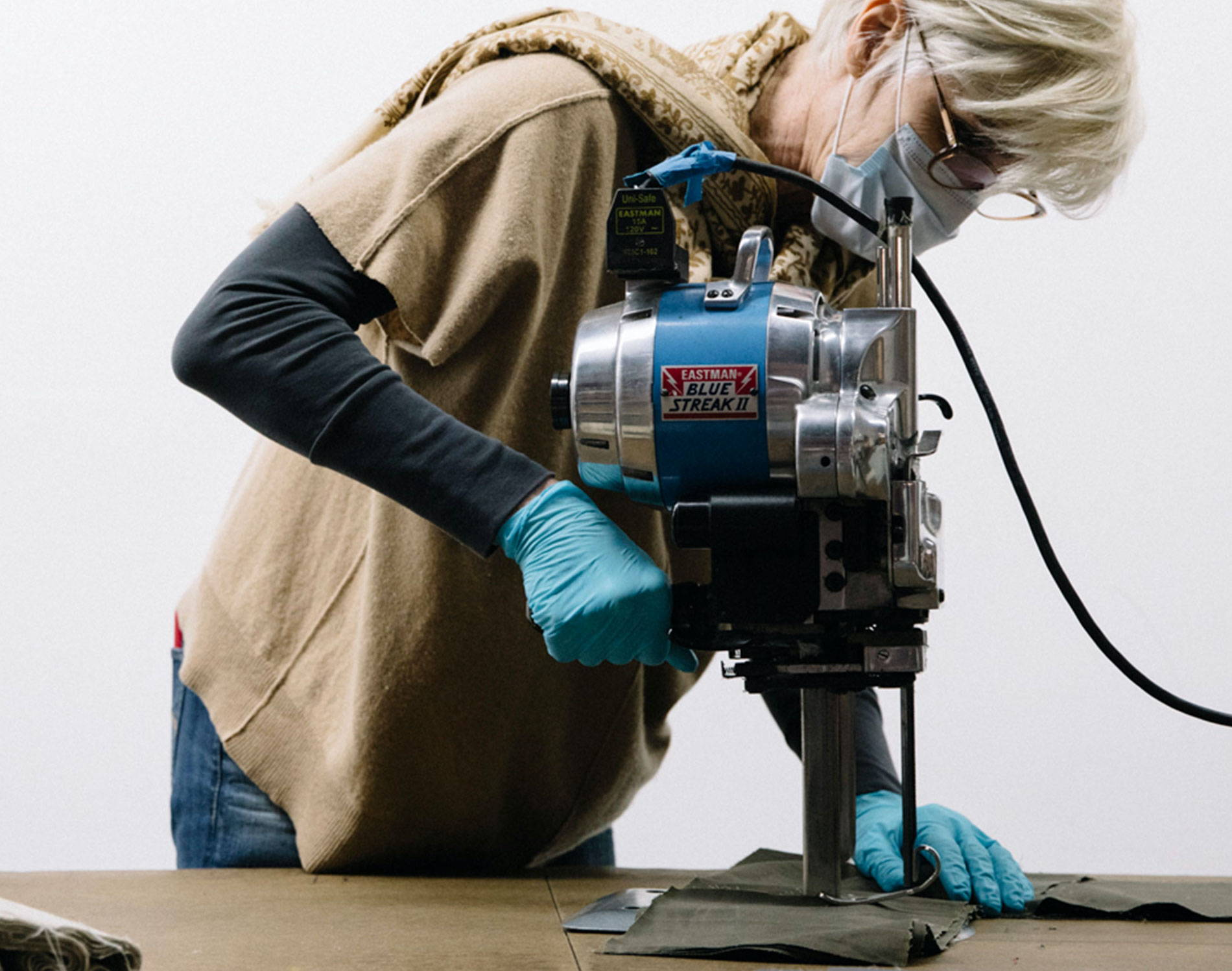 Image of Deborah Keiser (Timbuk2's President), cutting some material in a white room.