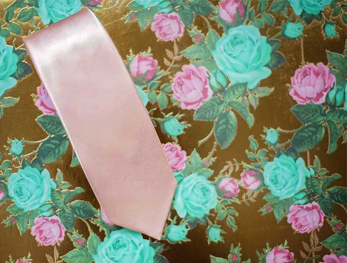 Blush pink solid wedding tie on a floral backdrop