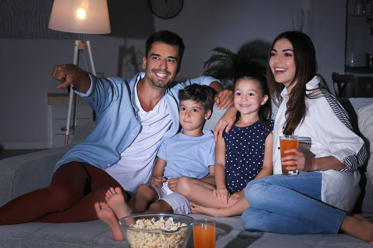 Young family enjoying a movie night at home on the sofa.